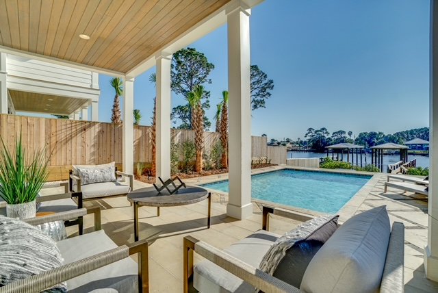 Deck in back yard with pool and water view